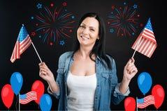 Donna contentissima attraente che tiene le bandiere degli Stati Uniti Fotografia Stock