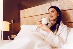 Donna contentissima che si rilassa alla camera di albergo Fotografia Stock Libera da Diritti