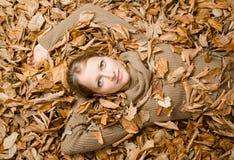 Donna coperta di fogli di autunno Fotografia Stock Libera da Diritti