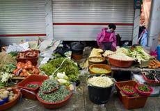Donna coreana anziana che vende le verdure sul mercato di strada fotografie stock