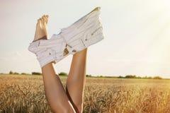 Donna in corona del grano che si spoglia gli shorts Cielo di estate sopra il campo Fotografie Stock