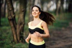 Donna corrente Corridore femminile che pareggia durante l'allenamento all'aperto in un parco Immagine Stock