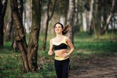 Donna corrente Corridore femminile che pareggia durante l'allenamento all'aperto in un parco Immagini Stock