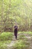 Donna corrente Corridore femminile che pareggia durante l'allenamento all'aperto in un parco Perdita di peso Fotografia Stock
