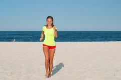 Donna corrente Corridore femminile che pareggia durante l'allenamento esterno sulla spiaggia Fotografia Stock