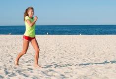 Donna corrente Corridore femminile che pareggia durante l'allenamento esterno sulla spiaggia Fotografia Stock Libera da Diritti