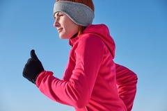 Donna corrente dell'atleta che sprinta durante l'esterno i di addestramento di inverno fotografia stock libera da diritti