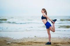 Donna corrente di giovane forma fisica che allunga sulla spiaggia Immagine Stock