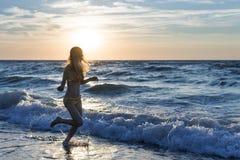 Donna corrente sulla spiaggia all'alba Fotografia Stock