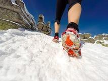 Donna corrente sulla traccia di inverno, sulla neve e sulle montagne bianche Immagini Stock Libere da Diritti