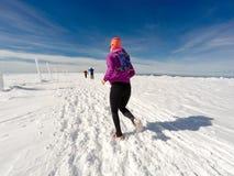 Donna corrente sulla traccia di inverno, sulla neve e sulle montagne bianche Immagine Stock