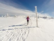 Donna corrente sulla traccia di inverno, sulla neve e sulle montagne bianche Fotografia Stock Libera da Diritti