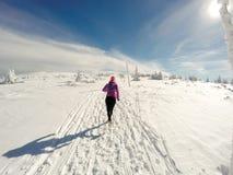 Donna corrente sulla traccia di inverno, sulla neve e sulle montagne bianche Immagini Stock