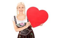 Donna in costume bavarese che tiene un cuore rosso Immagine Stock