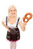 Donna in costume bavarese che tiene una ciambellina salata Fotografia Stock Libera da Diritti