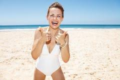 Donna in costume da bagno bianco alla spiaggia sabbiosa che mostra i pollici su Fotografie Stock Libere da Diritti