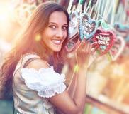 Donna in costume del Dirndl con il cuore del pan di zenzero Fotografie Stock Libere da Diritti