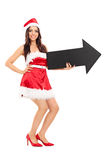 Donna in costume di Santa che tiene una freccia Immagine Stock Libera da Diritti
