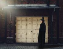 Donna in costume spaventoso nero di Halloween della strega con il vecchio muro di mattoni Immagine Stock
