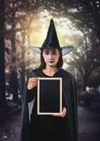 Donna in costume spaventoso nero di Halloween della strega, tenente il verro del gesso Immagini Stock