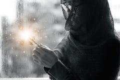Donna cristiana con l'incrocio in mani che prega speranza e culto sui precedenti della goccia di pioggia Illuminazione astratta B fotografia stock