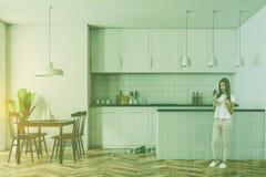 Donna in cucina bianca interna, tavola nera Immagine Stock