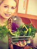 Donna in cucina che ha verdure che tengono cestino della spesa Immagine Stock