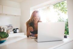 Donna in cucina che mangia le bacche e che per mezzo del computer portatile Fotografie Stock Libere da Diritti