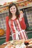 Donna in cucina che produce gli ossequi di Halloween Immagine Stock