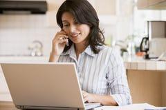 Donna in cucina con il computer portatile per mezzo del telefono cellulare Immagini Stock