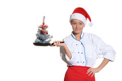 Donna-cucini con la vaschetta di frittura e l'albero di Natale fotografia stock