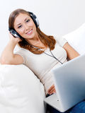 Donna in cuffia con il computer portatile Fotografie Stock