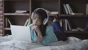 Donna in cuffie che lavorano ad un computer portatile archivi video