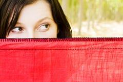 Donna curiosa dietro il velare immagine stock