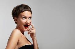 Donna curiosa sorridente divertente che indossa le labbra rosse Immagine Stock