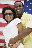 Donna d'abbraccio dell'uomo, bandiera americana nella priorità bassa Fotografie Stock