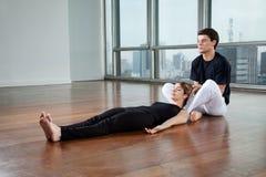 Donna d'aiuto dell'istruttore nell'esercizio di yoga Immagini Stock