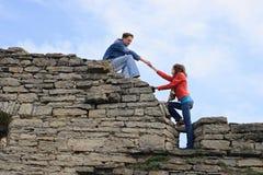 Donna d'aiuto dell'uomo per arrampicare parete Fotografie Stock Libere da Diritti