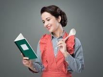 Donna d'annata con il libro di cucina fotografie stock libere da diritti