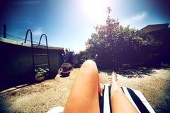 Donna d'annata delle gambe della foto che prende il sole nel giardino con il fondo dello stagno Immagini Stock Libere da Diritti