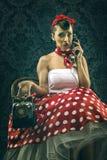 Donna d'annata, nella vecchia stanza con il telefono di quadrante Fotografie Stock