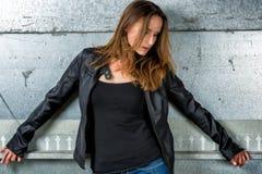 Donna d'avanguardia in blue jeans che posano nella metropolitana grungy Fotografia Stock