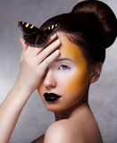Donna d'avanguardia con la farfalla. Luminosi creativi compongono. Orli neri Fotografia Stock