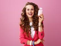 Donna d'avanguardia felice isolata sull'azienda agricola di mostra rosa yogurt organico Immagini Stock