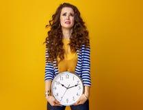 Donna d'avanguardia infelice isolata su giallo con l'orologio Immagine Stock