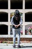 Donna da dietro contemplando la tomba di un caro immagine stock libera da diritti