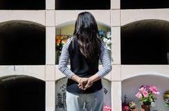 Donna da dietro contemplando la tomba di un caro fotografie stock