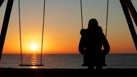 Donna da solo che oscilla contemplando tramonto sulla spiaggia stock footage