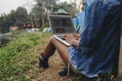 Donna da solo in natura facendo uso di un computer portatile su una fuga del campeggio da lavoro o dal concetto di dipendenza da  Immagine Stock Libera da Diritti
