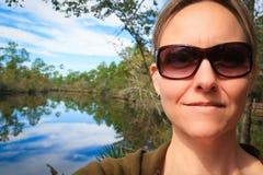 Donna da un fiume calmo Immagini Stock